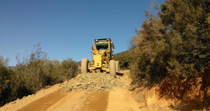 Motoniveladora limpiando terreno para realización de camino vecinal