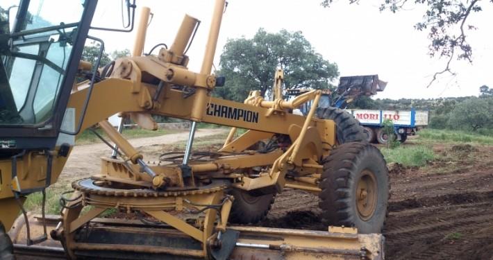 motoniveladora realizando trabajos de nivelación de terreno con camión al fondo