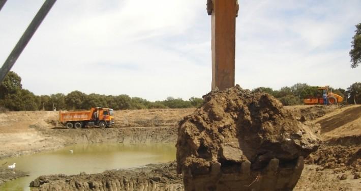 Trabajo de movimiento de tierras con retropalas, camiones y rodillo compactador