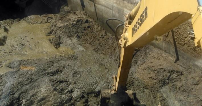 excavadora giratoria vaciando una fosa de lodos