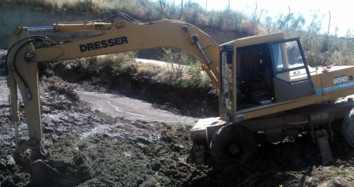 vaciado del barro de una fosa con excavadora giratoria